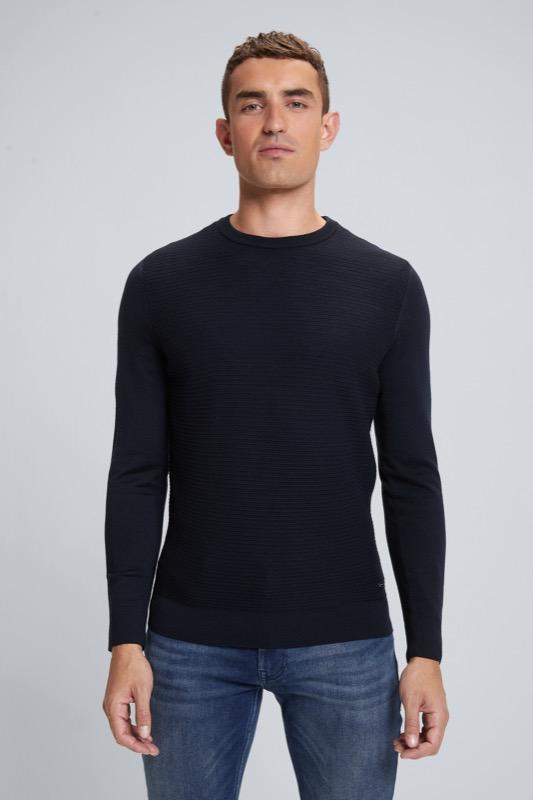 Artikel klicken und genauer betrachten! - Der Pullover Martin besteht aus einem Schurwoll-Mix im Merino-Strick, der sich auf der Vorderseite in markanter Struktur präsentiert. Ein gerippter Rundhalsausschnitt und ein dezentes Metallic-Badge runden das Piece ab. | im Online Shop kaufen